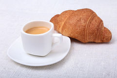 Crispy homemade fresh croissants and cup of coffee espresso on a white background, morning breakfast, selective focus Royalty Free Stock Image