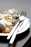 Crispy indulgence. An almond croissant on a white plate with a knife and fork on the side Royalty Free Stock Photo