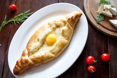 Crispy khachapuri on a white plate with tomatoes and cheese, top view royalty free stock photos