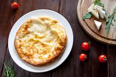 Crispy khachapuri on wooden stle on a white plate with tomatoes and cheese, top view stock photo