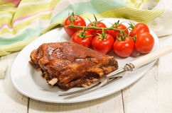Crispy marinated ribs and fresh tomatoes on an oval plate Stock Photo