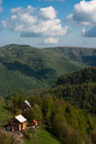 Crispy morning. Taken in mid-May somewhere in the Romanian Carpathians. A few clouds, a rich, green forest and a secluded house in the middle of nowhere Stock Photo