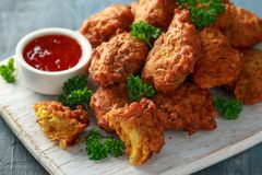 Crispy onion bhajis with sweet chilli sauce on white wooden board stock images