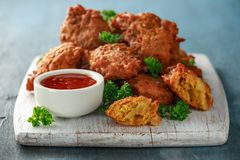 Crispy onion bhajis with sweet chilli sauce on white wooden board stock photography