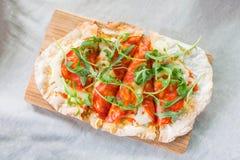 Crispy pan pizza on wooden plate. Crispy pepperoni pizza on wooden plate royalty free stock photo