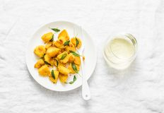 Crispy polenta crust potatoes baked with sage butter and a glass of white wine on a light background Royalty Free Stock Images