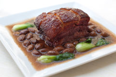 Crispy pork belly and beans. Served with kale on a plate Stock Photography