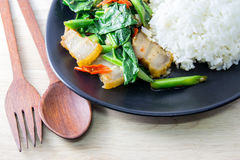 Crispy Pork with Kale on wood desk with spoon and fork stock photos