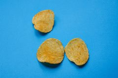 crispy potato chips on blue background. nachos chips stock photos