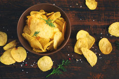 Crispy potato chips in a cup on a dark background, tinted Stock Images