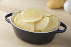 Crispy potato chips in dark blue bowl. On wooden boards stock images