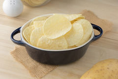 Crispy potato chips in dark blue bowl. On wooden boards royalty free stock photos