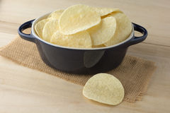 Crispy potato chips in dark blue bowl. On wooden boards stock photo