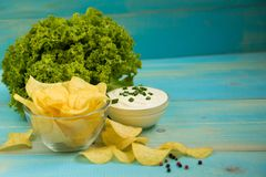 Potato chips homemade. Crispy potato chips in a glass bowl with sour cream, salad and pepper on old blue wooden background. Potato chips homemade stock photography