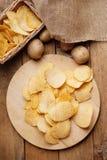 Crispy potato chips and potato Royalty Free Stock Images