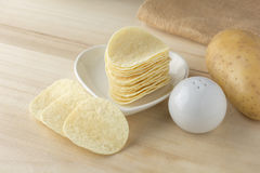 Crispy potato chips in white dish. On wooden boards stock photo