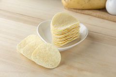 Crispy potato chips in white dish. On wooden boards royalty free stock image