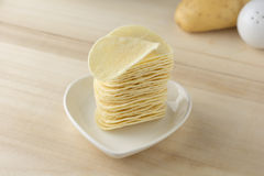 Crispy potato chips in white dish. On wooden boards stock photos