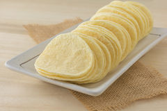 Crispy potato chips in white dish. On wooden boards stock image
