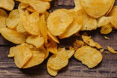 crispy potato chips on wooden background. chips started stock photos