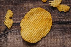 crispy potato chips on wooden background. chips started stock image