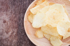 Crispy potato chips on wooden background Stock Images