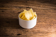 Crispy potato chips on wooden background Royalty Free Stock Photos