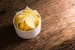 Crispy potato chips on wooden background Stock Image