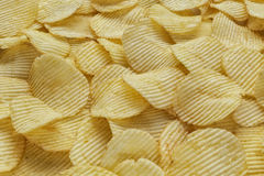 Crispy ribbed potato chips. Background made of ribbed potato chips Royalty Free Stock Photography