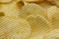 Crispy ribbed potato chips. Background made of ribbed potato chips Royalty Free Stock Photo