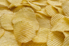 Crispy ribbed potato chips. Background made of ribbed potato chips Stock Photography
