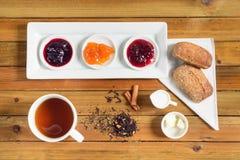 Crispy rolki z masłem, dżemem i gorącą herbatą dla śniadania, Fotografia Royalty Free