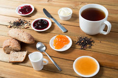 Crispy rolls with butter, apple jam and hot tea for breakfast Stock Photo