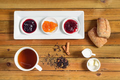 Crispy rolls with butter, apple jelly and hot tea for breakfast Stock Images