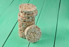Crispy round dietary buckwheat rice fitness bread on green wooden table. Food for weight loss.  Stock Photography