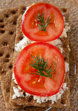 Crispy rye bread, cheese, tomato and herbs Royalty Free Stock Images