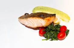 Crispy skin atlantic salmon fillet with pesto mayonnaise, spinach, lemon & grape tomato. royalty free stock images