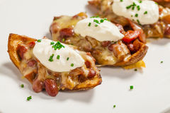 Crispy skin potato. Es with kidney bean & tomato salsa with sour cream and chives Stock Photos