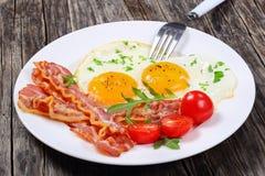 Crispy smażący bekonowy i jajka na talerzu Fotografia Royalty Free