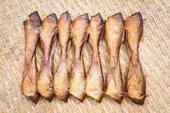 Crispy smoke dried siamese mud carp fish. Close up Crispy smoke dried siamese mud carp fish on bamboo threshing basket Royalty Free Stock Image