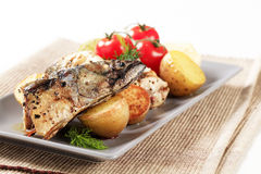 Crispy spiced mackerel with potatoes. Pieces of crispy spiced mackerel with new potatoes Stock Photography