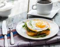 Crispy toast with a fried egg and fresh arugula, a cup of coffee Stock Photos