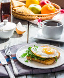 Crispy toast with a fried egg and green arugula, coffee cup, fru Royalty Free Stock Images