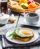 Crispy toast with a fried egg and green arugula, coffee cup, fru Royalty Free Stock Photo