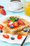 Crispy toast with honey, fresh strawberries and blueberries Stock Images