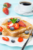 Crispy toast with honey, fresh strawberries and blueberries Royalty Free Stock Photography