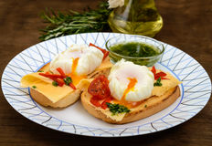 Crispy toast with poached egg, cheese, peppers, tomatoes, souse on a plate Stock Images