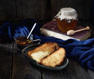 Crispy toast and tea in a vintage mug, honey and book on a wooden background Royalty Free Stock Photography