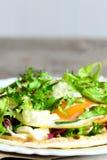 Crispy tortilla z jajkiem, hummus i sałatką na talerzu smażącymi, Zdrowy i szybki jarski tortilla przepis Pionowo fotografia zbli Obraz Royalty Free