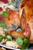 Crispy turkey. Closeup of roasted turkey served with herbs, baked potatos and walnuts on holliday table Royalty Free Stock Photo
